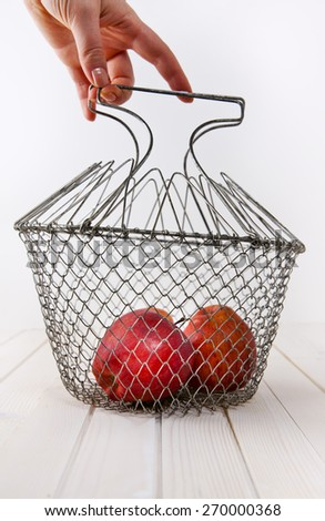 apples in basket in hand  - stock photo