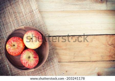 Apples in basket on wooden table  - stock photo