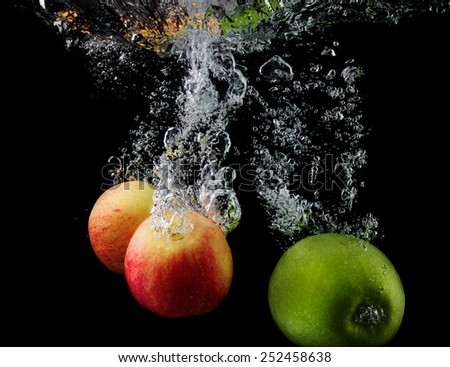 Apples in water with air bubbles on a black background. - stock photo