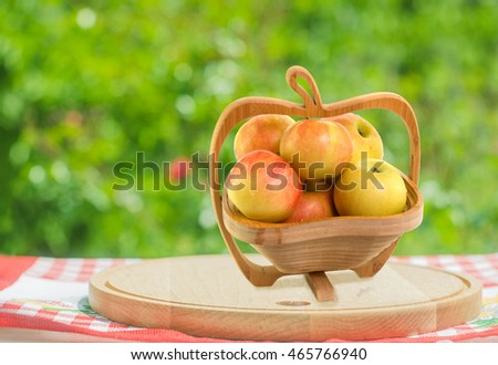 apples in wooden bowl on cutting board in garden