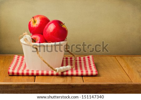 Apples in wooden bucket on tablecloth over vintage background - stock photo