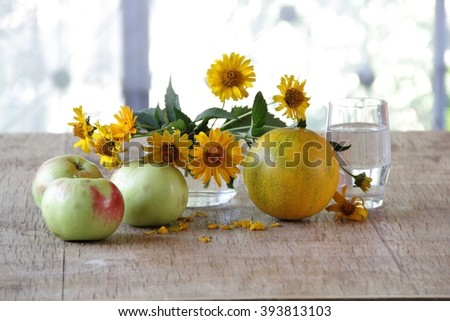 apples, melon and a bouquet of yellow daisies on a wooden table