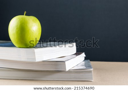 Apples on a pile of books on a table with black background