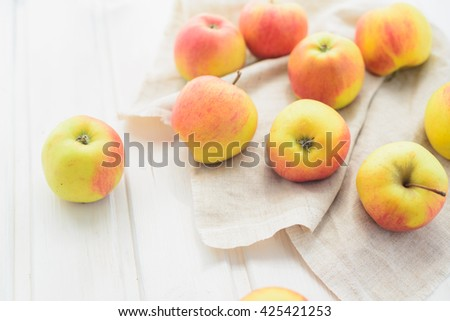 apples on a white rag on the gray wooden background top view, rustic concept