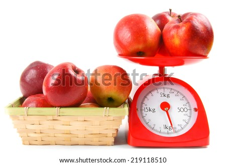 Apples on scales and in a basket on a white background. - stock photo