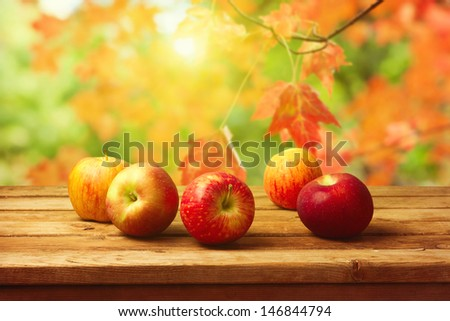 Apples on wooden table over autumn bokeh background - stock photo
