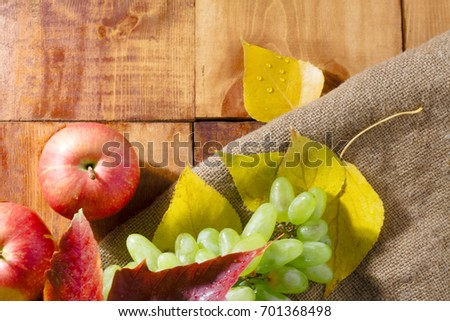 Apples on wooden table with autumn on wooden background