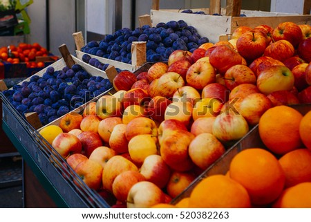 Apples, oranges and plums for sale at a market