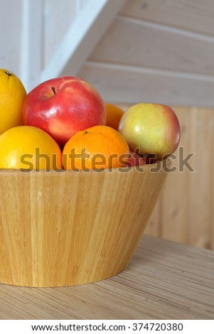 apples, oranges and tangerines in a wooden vase - stock photo