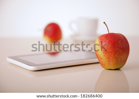 apples, tablet pc and coffee cup on table - stock photo