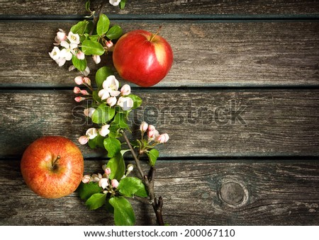 Apples with flowers on wooden board - stock photo