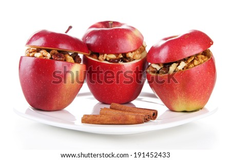 Apples with raisins and nuts on plate isolated on white
