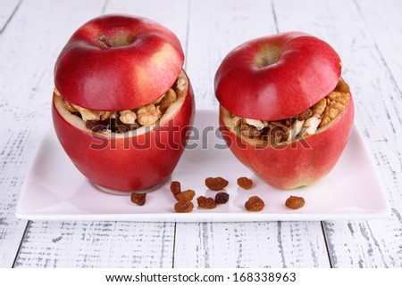 Apples with raisins and nuts on plate on wooden background