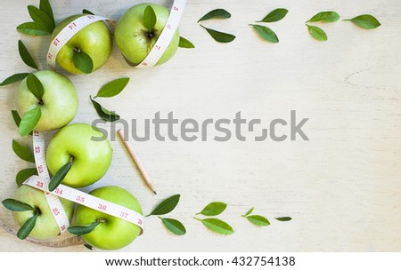Apples with tape measure on white wood background, lose weight concept