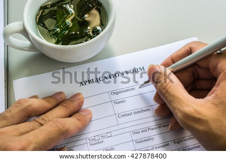 application form with tea cup - stock photo