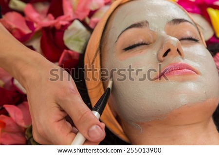 Application of rejuvenating mask on the face of the girl. Cosmetic procedures for the face. Hands beautician applied mask on face of the girl. Facial treatment in a beauty salon. - stock photo