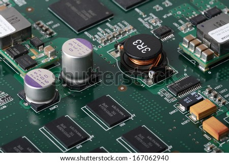Application Specific Integrated Circuit, inductors, chip capacitors, electrolytic capacitors, Double Data Rate Synchronous Dynamic Random-access chips and resistors mounted on a Printed Wiring Board