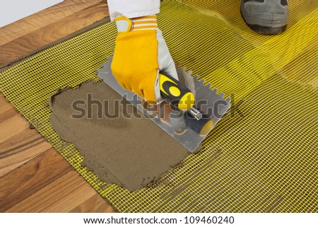 applies tile adhesive on wooden floor with reinforcement mesh - stock photo
