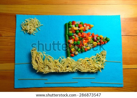 Applique of food in the form of a ship at sea on a blue cloth on a wooden kitchen table (soft focus)