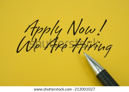 Apply Now! We Are Hiring note with pen on yellow background