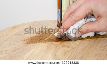 Applying a dark oak stain onto wood using a cloth. - stock photo