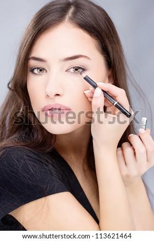 applying cosmetic pencil on woman's eye - stock photo