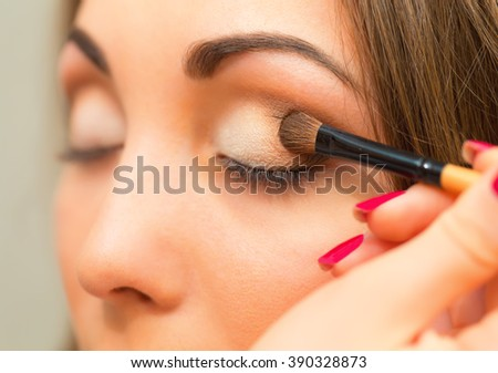 Applying eye makeup products on girls face.