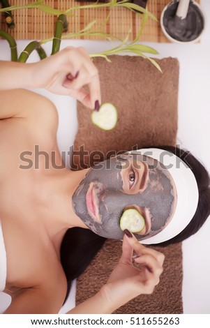 Applying facial mask at woman face at beauty salon