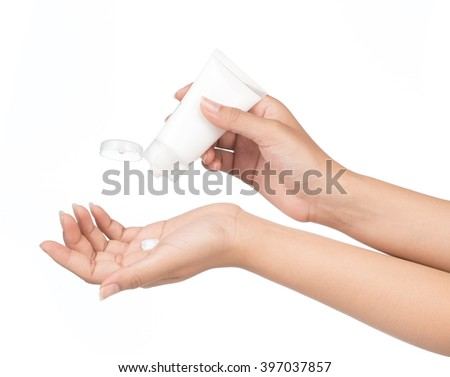 Applying hand moisturizer cream on female hands isolated on white background