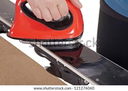 applying hot wax to downhill ski base with iron - stock photo