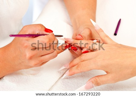 Applying long, sharp artificial nails to a woman in beauty salon by a manicurist.