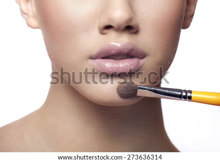Applying make up liquid powder with brush blusher - stock photo