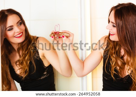 Applying makeup funny idea. Young pretty woman drawing heart sign symbol on mirror in bathroom. - stock photo