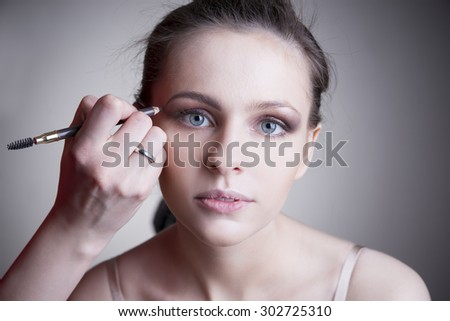 Applying makeup. Portrait of a beautiful young woman on a gray background. Professional make-up and hairstyle