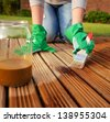 Applying protective varnish on a patio wooden floor - stock photo