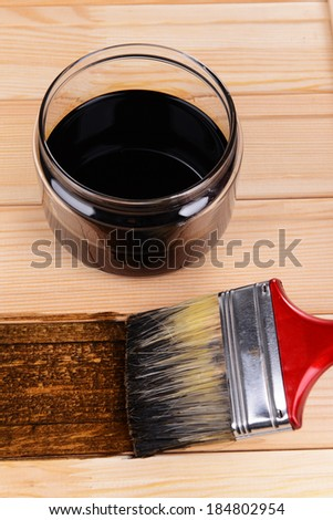 Applying protective varnish to wooden board close-up - stock photo
