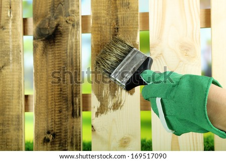 Applying protective varnish to wooden fence, on bright background - stock photo