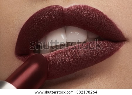 Applying red lipstick on lips in close up photo in studio lighting - stock photo