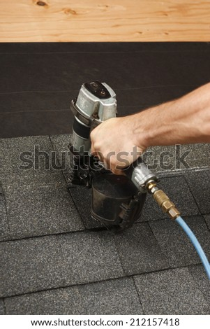 Applying roof shingles with a gun - stock photo