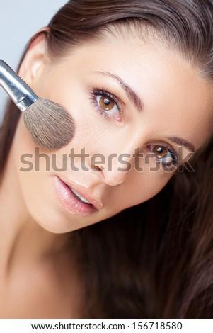 Applying shimmer powder - stock photo