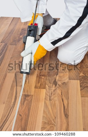 Applying silicone sealant in spaces of old wooden floor - stock photo