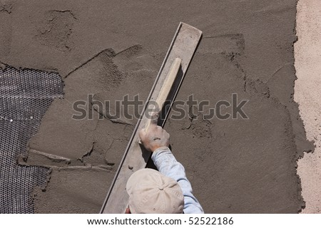 Applying stucco to wall with metal lath support. Focus mainly on stucco and lath. - stock photo