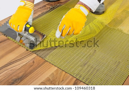 applying tile adhesive with reinforcement mesh on wooden floor - stock photo
