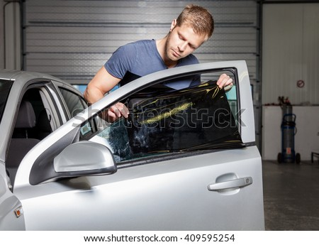 Applying tinting foil onto a car window in a workshop - stock photo