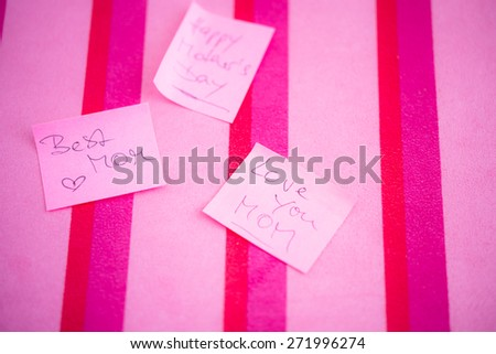 Appreciation message to Happy Mother's Day on pink sticky notes  Best Mom, Love you Mom handwritten text on paper, red magenta fuchsia striped background. Shallow depth of field, blurred - stock photo