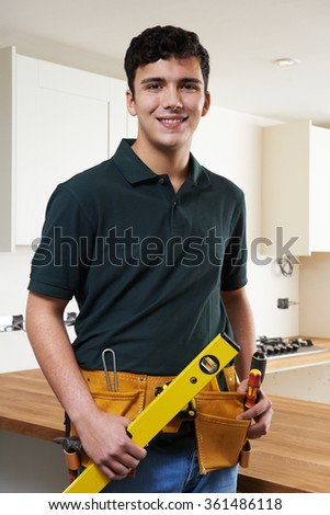 Apprentice Carpenter Installing Luxury Fitted Kitchen - stock photo