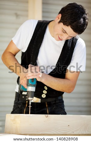 Apprentice is drilling holes at construction site - stock photo