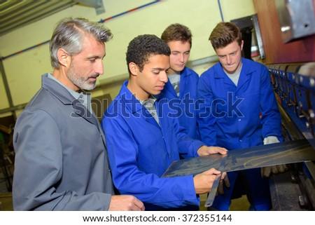 Apprentice measuring a piece of flat metal - stock photo