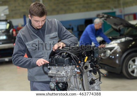apprentice mechanic in auto shop working on car engine