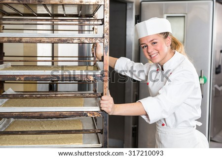 Apprentice or worker in bakery push Rack with dough in oven